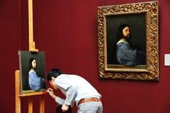 L'uomo sta dipingendo in un museo immagini stock