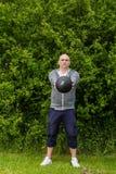 L'uomo sta esercitandosi all'aperto con una palla medica da 3 chilogrammi Fotografie Stock Libere da Diritti