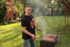 L'uomo sta friggendo il raduno in giardino Alimento sullo spiedo, griglia, barbecue immagini stock libere da diritti