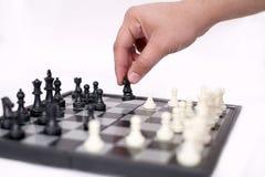 L'uomo sta giocando il pegno della tenuta e di scacchi immagini stock