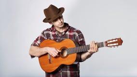 L'uomo sta giocando la chitarra in cappello su bianco Immagine Stock