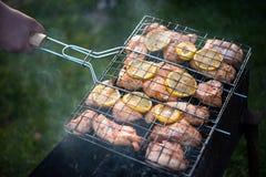 L'uomo sta girando la cottura della griglia con il pollo Immagini Stock Libere da Diritti