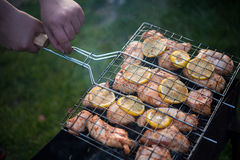 L'uomo sta girando la cottura della griglia con il pollo Fotografie Stock