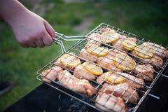 L'uomo sta girando la cottura della griglia con il pollo Immagine Stock Libera da Diritti