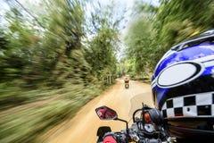 L'uomo sta guidando un motociclo sulla strada Fotografia Stock