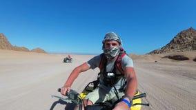 L'uomo sta guidando una bici del quadrato in deserto dell'Egitto e sta sparandosi su una macchina fotografica di azione video d archivio