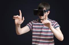 L'uomo sta indossando la cuffia avricolare di realtà virtuale 3D e sta toccando qualcosa Fotografie Stock