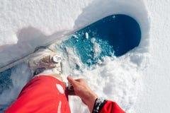 L'uomo sta indossando uno snowboard Immagini Stock