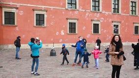 L'uomo sta intrattenendo i bambini con le grandi bolle di sapone nel quadrato del castello di Città Vecchia video d archivio