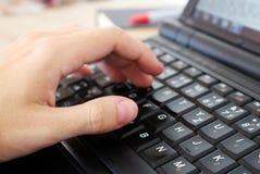 L'uomo sta lavorando con il computer portatile nell'ufficio Immagini Stock Libere da Diritti