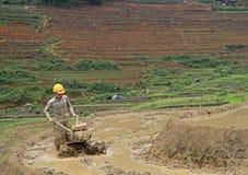 L'uomo sta lavorando il suolo dal coltivatore manuale dentro Fotografia Stock