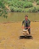 L'uomo sta lavorando il suolo dal coltivatore manuale dentro Immagine Stock Libera da Diritti