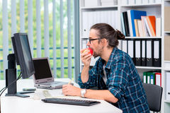L'uomo sta lavorando nel suo officeand che mangia la mela Fotografia Stock