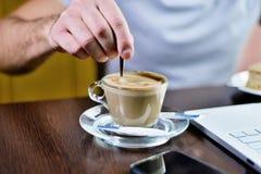 L'uomo sta mescolando il cucchiaio dello zucchero in tazza del caffè del cappuccino fotografia stock libera da diritti