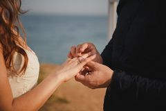L'uomo sta mettendo la fede nuziale sulla sua mano del ` s della sposa, fine su La cerimonia di nozze all'aperto della spiaggia,  Fotografia Stock Libera da Diritti