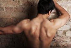 L'uomo sta mostrando i suoi muscoli Fotografia Stock Libera da Diritti