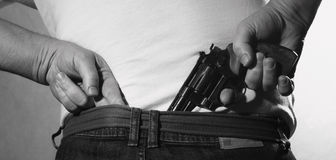 L'uomo sta nascondendo una pistola a sua indietro Fotografia Stock Libera da Diritti