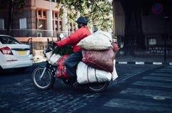 L'uomo sta portando le merci sulla sua bici - foto di riserva Immagine Stock
