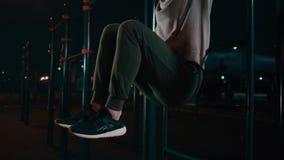 L'uomo sta preparando i muscoli addominali sollevando le gambe sulla barra orizzontale all'aperto archivi video