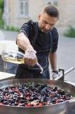 l'uomo, sta preparando le cozze su una grande padella sulla via, versa il vino bianco Immagini Stock Libere da Diritti