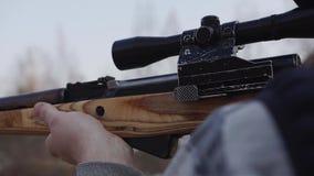 L'uomo sta preparando sparare un fucile di tiratore franco Sta guardando con la portata stock footage