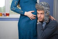 L'uomo sta provando ad ascoltare la pancia della sua moglie fotografie stock
