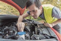 L'uomo sta riparando l'automobile e sta controllando il liquido refrigerante del motore fotografia stock