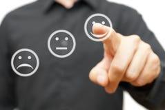 L'uomo sta scegliendo l'icona felice e positiva di sorriso, concetto del satisfacti Fotografie Stock Libere da Diritti