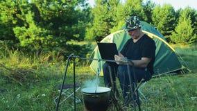 L'uomo sta sedendosi alla tenda, guardando il giocatore di bocce appendere sopra il fuoco e scrivere sulla tastiera del ` s del c stock footage