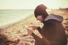 L'uomo sta sedendosi e sta tenendo un telefono Fotografie Stock Libere da Diritti
