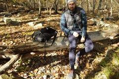 L'uomo sta sedendosi nella foresta di autunno nelle montagne Escursione e viaggiare Fotografie Stock