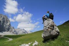L'uomo sta sedendosi su una pietra Fotografia Stock