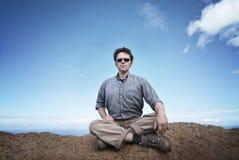 L'uomo sta sedendosi su una roccia Fotografia Stock Libera da Diritti