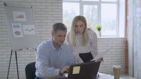 L'uomo sta sedendosi su una sedia in ufficio e la giovane donna sta stando vicino, sia sta considerando una carta su una tavola,  video d archivio