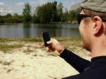 L'uomo sta sedendosi sulla spiaggia nel lago e sulla scrittura sms sul suo Smart Phone Fotografie Stock Libere da Diritti
