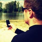 L'uomo sta sedendosi sulla spiaggia nel lago e sulla scrittura sms sul suo Smart Phone Immagine Stock Libera da Diritti