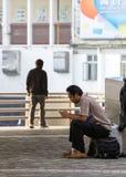 L'uomo sta sedendosi sullo Zaino e sta utilizzando lo smartphone fotografie stock
