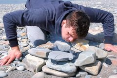 L'uomo sta soffiando sui carboni nel falò sulla spiaggia di pietra Fabbricazione del falò della città universitaria fotografia stock