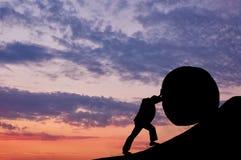 L'uomo sta spingendo verso l'alto la pietra Fotografia Stock