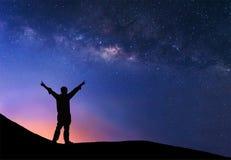 L'uomo sta stando accanto alla galassia della Via Lattea con i suoi rais delle mani Fotografia Stock Libera da Diritti