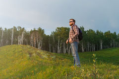L'uomo sta su una collina e sulla sorveglianza del tramonto fotografia stock