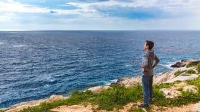 L'uomo sta sull'orlo dell'abisso ed esamina il mare fotografia stock