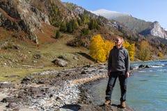 L'uomo sta sulla Banca del fiume di Katun nelle montagne di Altai Fotografia Stock
