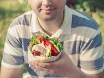 L'uomo sta tenendo il panino del falafel in sacco di carta Fotografia Stock