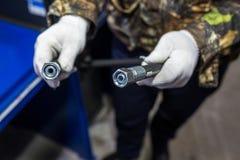 L'uomo sta tenendo un tubo flessibile ad alta pressione con i montaggi immagini stock