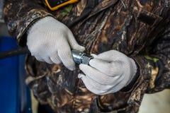 L'uomo sta tenendo un tubo flessibile ad alta pressione con i montaggi fotografia stock