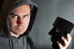 L'uomo sta tenendo una maschera in sua mano Fotografie Stock Libere da Diritti