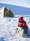 L'uomo sta trovandosi in un sacco a pelo vicino alla tenda Immagini Stock Libere da Diritti