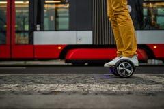L'uomo sta usando il hoverboard contro lo sfondo del tram Fotografie Stock