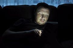 L'uomo sta utilizzando il cuscinetto di tocco sul sofà Immagine Stock